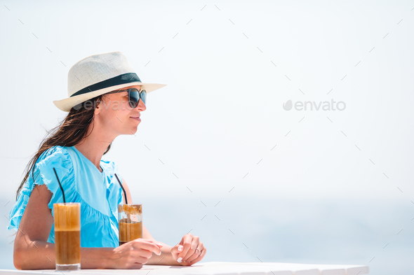 Young woman drinking cold coffee enjoying sea view - Stock Photo - Images