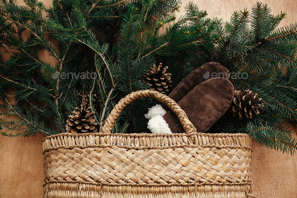 Rustic basket with fir branches, cozy gloves, cones on rustic wooden background - Stock Photo - Images