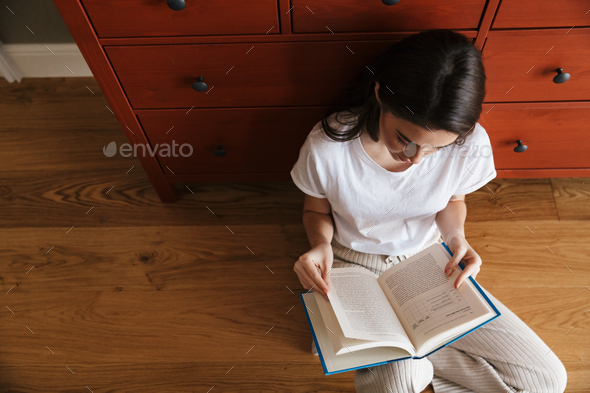 Attractive young brunette woman reading a book - Stock Photo - Images