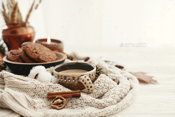 Hygge lifestyle, cozy autumn mood. Coffee cup, chocolate cookies, candle and fall leaves - Stock Photo - Images