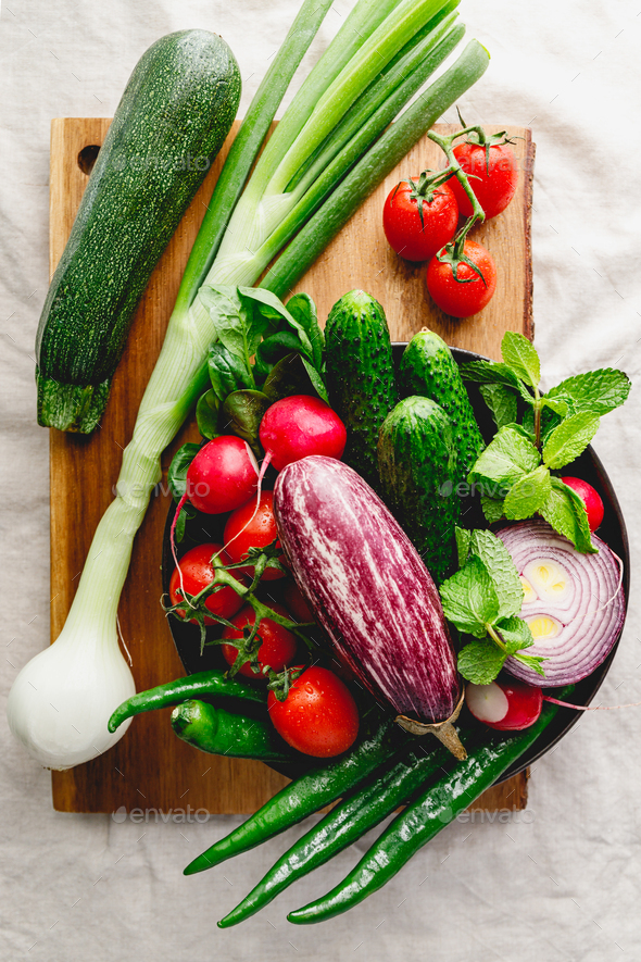 Different fresh vibrant vegetables in a plate on a wooden tray - Stock Photo - Images