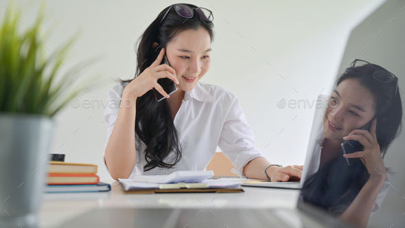 A smiling young woman using a smartphone to make business contacts - Stock Photo - Images