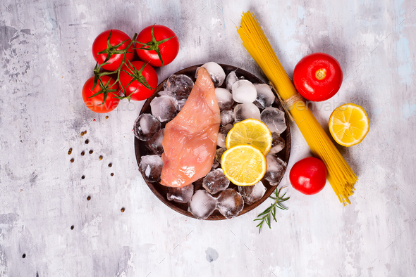 Pasta ingredients. Chicken breasts, tomatoes, spaghetti pasta, and lemon on the stone table - Stock Photo - Images