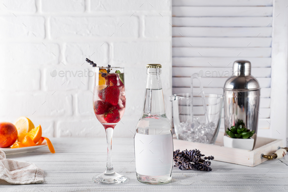 Red Cocktail with ice and strawberry, ginger and lavender with a bottle of tonic and a place under - Stock Photo - Images
