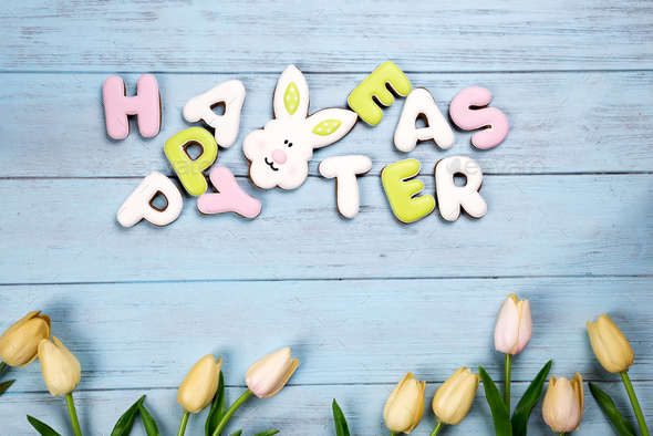 Happy Easter colorful lettering Happy Easter of ginger biscuits and cookies bunny on wooden blue - Stock Photo - Images