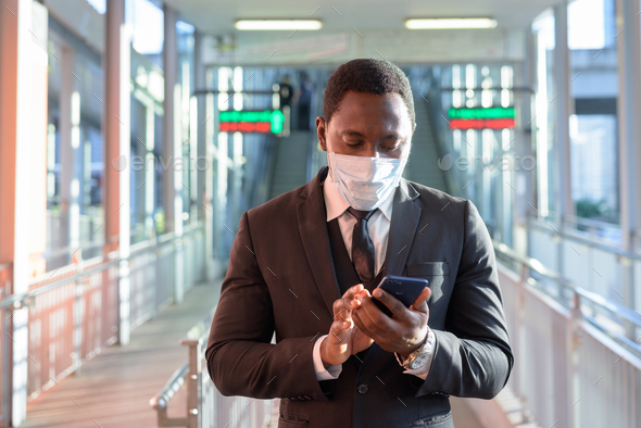 Portrait of African businessman with mask using phone at the train station outdoors - Stock Photo - Images
