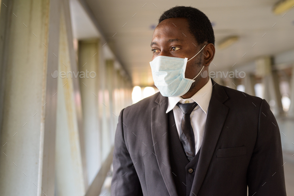 Portrait of African businessman with mask looking at view of the city at the footbridge - Stock Photo - Images