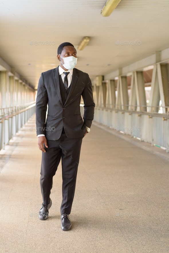 Full body shot of African businessman with mask walking at the footbridge - Stock Photo - Images
