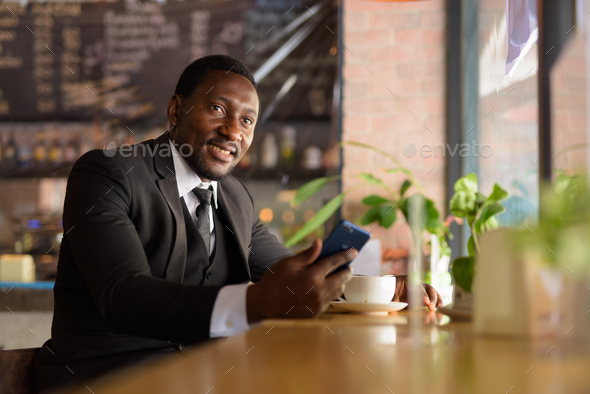 Happy bearded African businessman thinking while using phone at the coffee shop - Stock Photo - Images