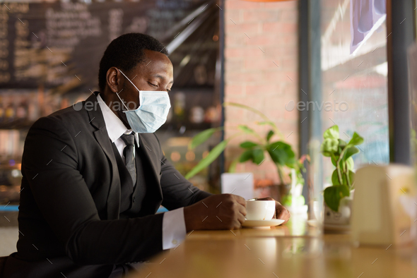 Portrait of African businessman wearing mask while drinking coffee inside the coffee shop as the new - Stock Photo - Images