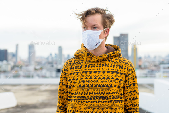 Young man with hoodie wearing mask and thinking against view of the city - Stock Photo - Images