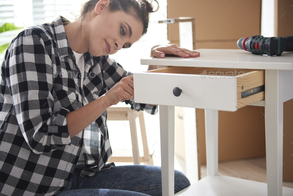 Young woman renovating a night table - Stock Photo - Images
