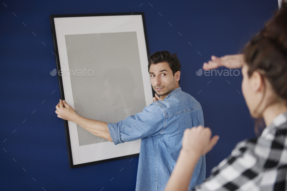 Couple hanging a picture frame on the blue wall - Stock Photo - Images