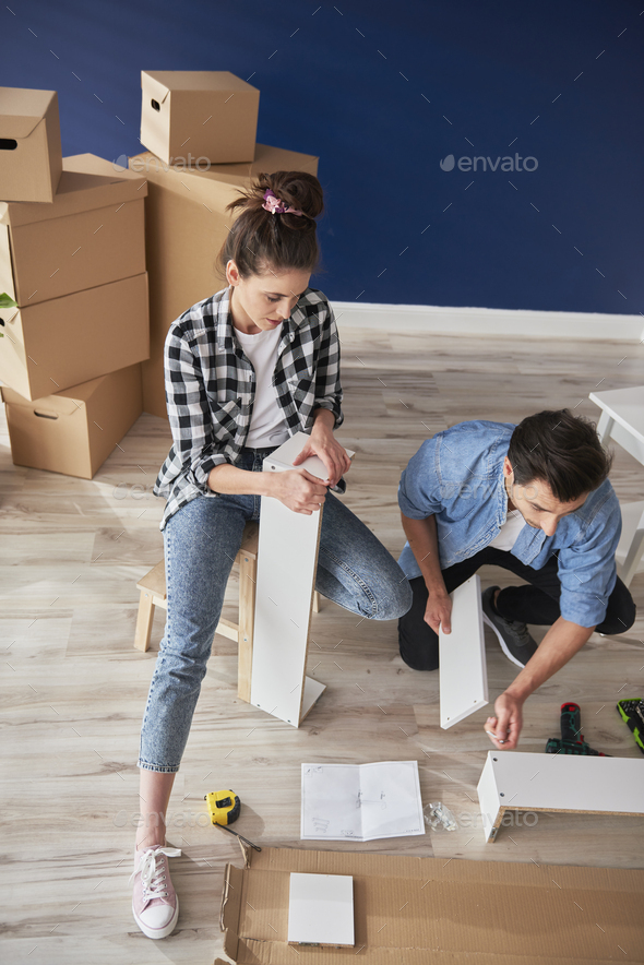 Top view of couple having problem with installing furniture - Stock Photo - Images