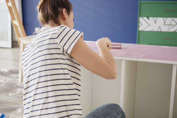 Young woman repainting old furnitures - Stock Photo - Images
