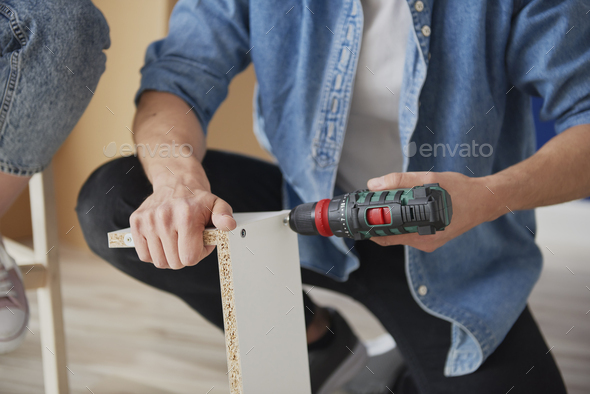 Unrecognizable man installing furniture for new house - Stock Photo - Images