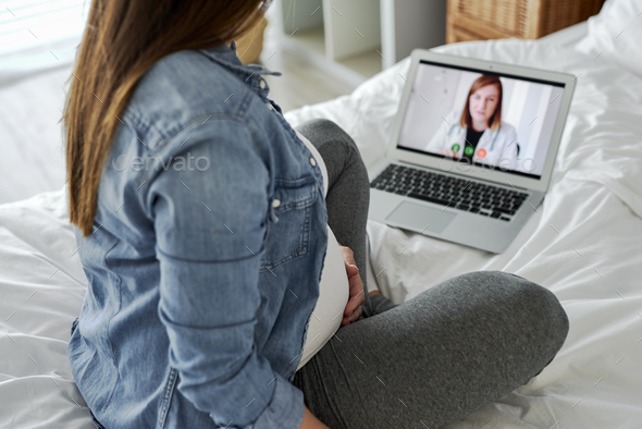 Woman in advanced pregnancy having video conference with doctor - Stock Photo - Images
