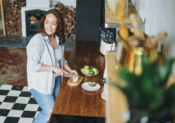 Adult smiling brunette woman in casual clothes cuts avocado in kitchen at home - Stock Photo - Images