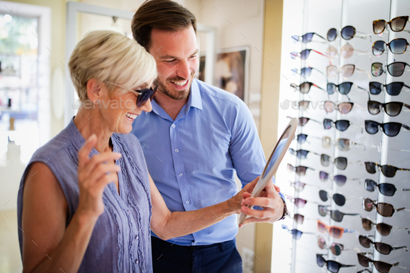 Pretty mature woman is choosing new glasses at optics store - Stock Photo - Images
