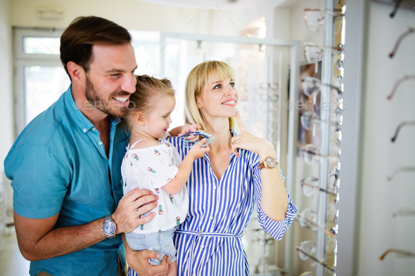 Happy mother and father choosing eyeglasses frame with their daughter in optical store - Stock Photo - Images