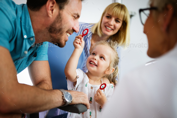 Ophthalmologist is checking the eye vision of little cute girl in modern clinic - Stock Photo - Images