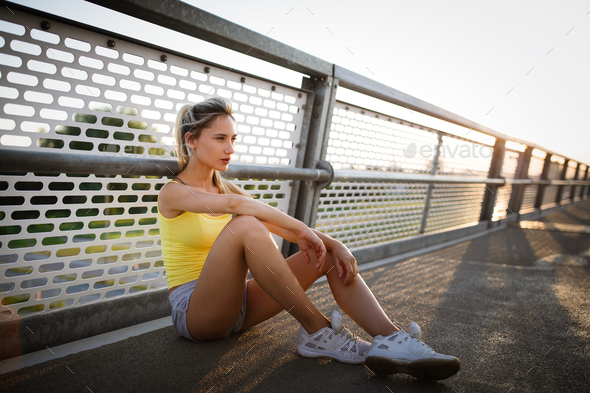 Portrait of fit cheerful blonde woman resting after a run in a city - Stock Photo - Images