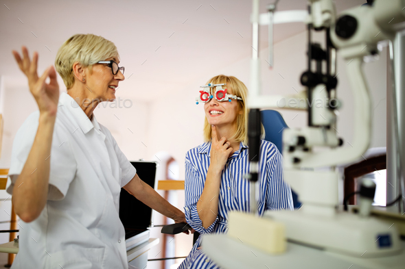 Young woman taking an eyesight test examination at an optician clinic - Stock Photo - Images