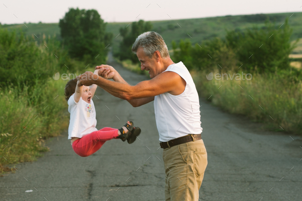 Grandfather with grandchild summer time together playing - Stock Photo - Images