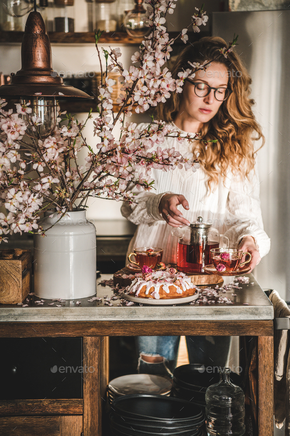 Young woman serving homemade bundt cake and tea in kitchen - Stock Photo - Images