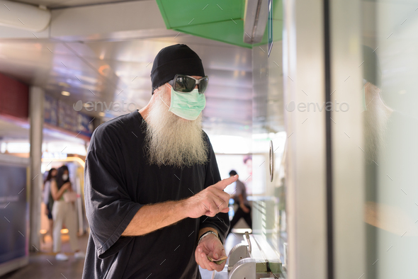 Mature bearded hipster man with mask and sunglasses buying ticket at the sky train station - Stock Photo - Images