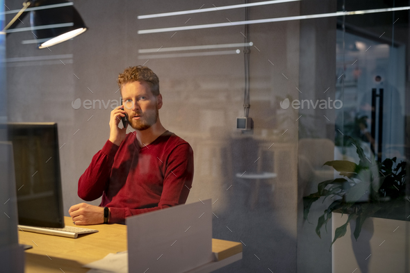 Worried business man talking on phone late in office - Stock Photo - Images