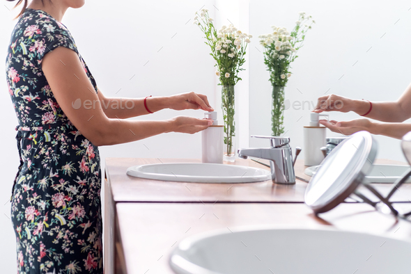 Woman washing her hands with soap at her bathroom - Stock Photo - Images