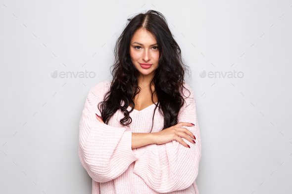 beautiful young woman standing with arms crossed and attitude - Stock Photo - Images