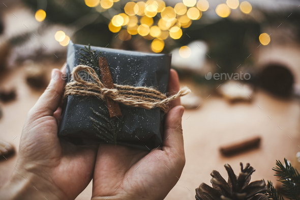 Hands holding rustic christmas gift in black wrapping paper - Stock Photo - Images