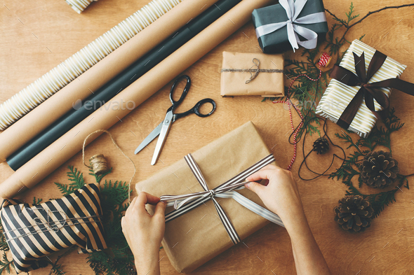 Merry Christmas, flat lay. Hands wrapping stylish christmas gift box - Stock Photo - Images