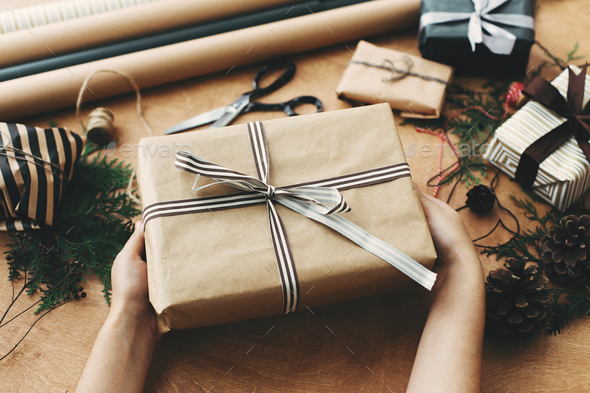 Hands Holding Stylish Christmas Gift Box In Craft Paper And Scissors Rustic Presents Stock Photo By Sonyachny