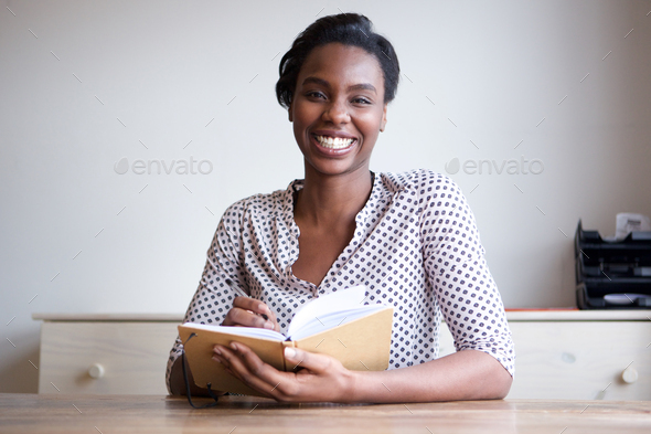 smiling black woman at home writing in journal - Stock Photo - Images