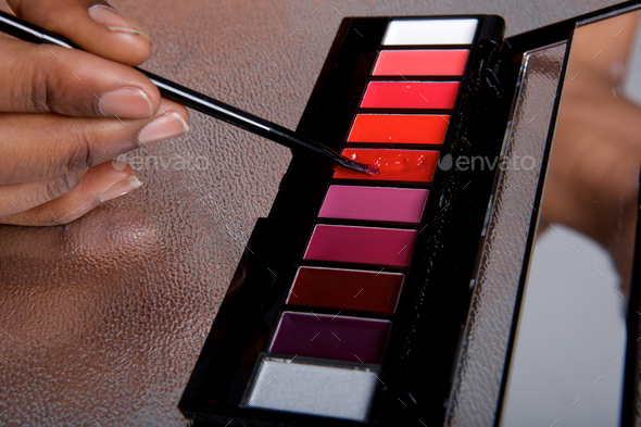 Close up lip gloss color palette and woman holding makeup brush - Stock Photo - Images