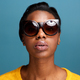 stylish young black woman in sunglasses by blue wall - PhotoDune Item for Sale