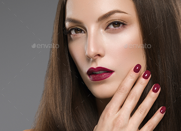 Beautiful brunette woman red lips manicure with long hair natural makeup face closeup. Studio - Stock Photo - Images