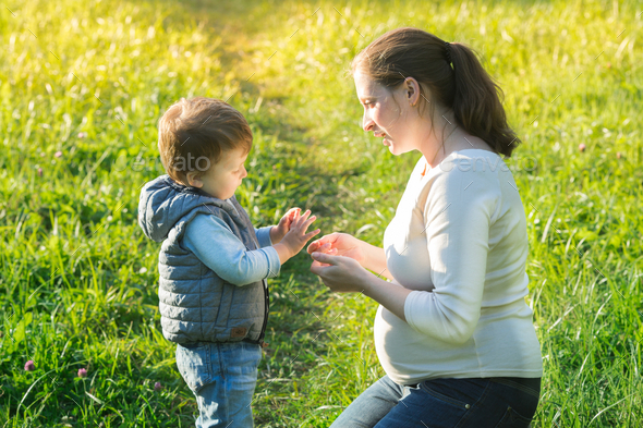 Young family. Mother with her son are sitting on the grass in the park. Summer time. Outdoor filming - Stock Photo - Images