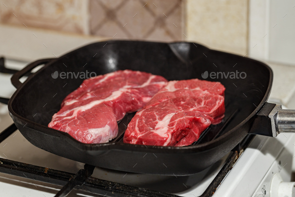 Raw beef steak in grill pan - Stock Photo - Images