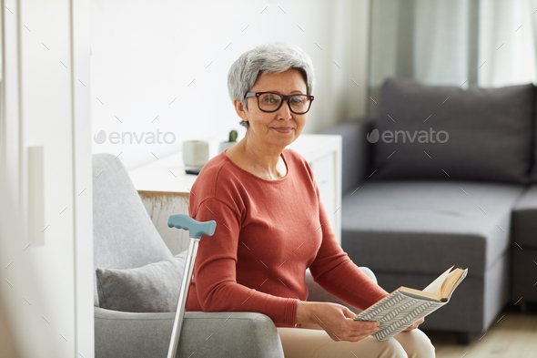 Woman resting with book at home - Stock Photo - Images