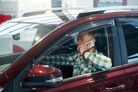 Happy man using phone in car in dealership - Stock Photo - Images