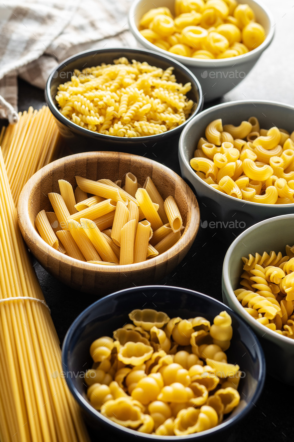 Various types of raw italian pasta in bowls. - Stock Photo - Images