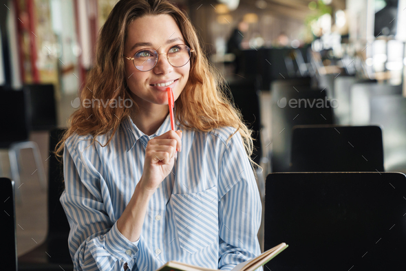 Image of cheerful woman smiling and writing on planner while sitting - Stock Photo - Images