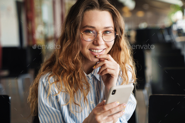 Image of cheerful young woman laughing and typing on cellphone - Stock Photo - Images