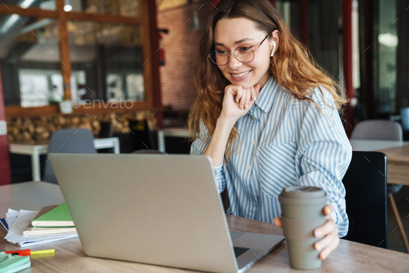 Image of woman drinking coffee while using laptop and wireless earphones - Stock Photo - Images