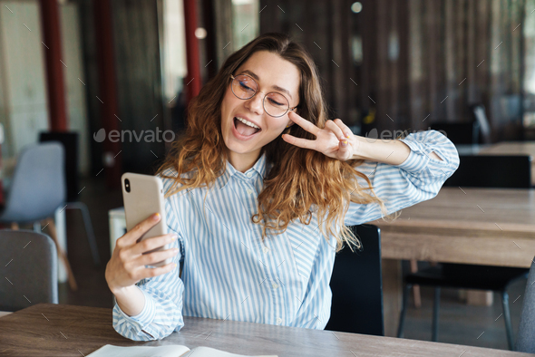 Image of woman gesturing peace sign and taking selfie on cellphone - Stock Photo - Images