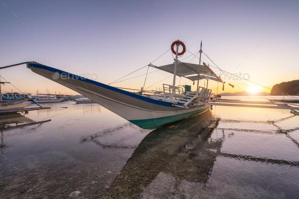 Trip long banca boat on Corong corong beach, sunset flare shine. El Nido, Philippines - Stock Photo - Images